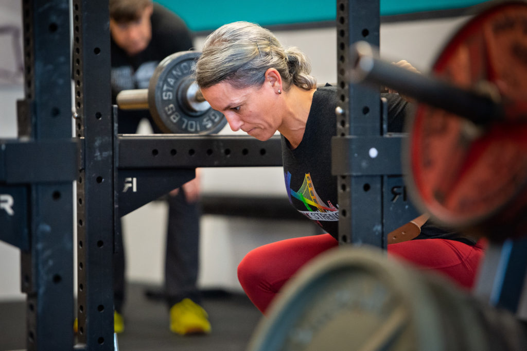 Lifter squatting with coach watching